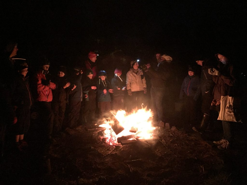 Cubs and Leader around a bonfire